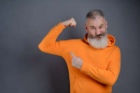 Mature bearded man dressed orange hoodie shows muscles after practising over gray studio background, look I am very strong and healthy, perfect biceps