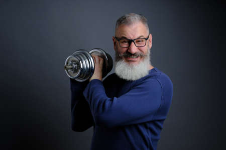 Bearded mature man with dumbbell. Male with dumbbell during exercise. Sport, workout, fitness, healthy lifestyle concept.