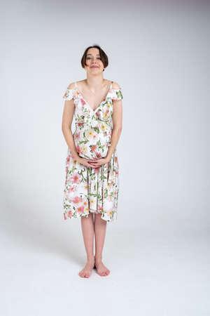 Studio portrait of cheerful young pregnant woman in summer dress on white grey background, happy pregnancy concept Archivio Fotografico