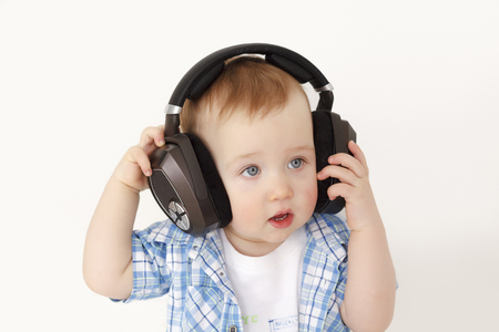 anticipation: Little boy listening to music on headphones Stock Photo