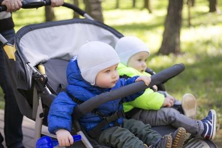 街でベビーカーで 2 つの男の子双子