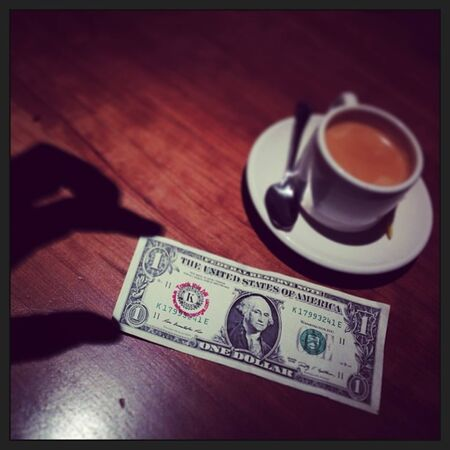 Shadowy hand seizes the moment and a dollar bill.