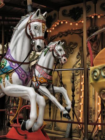 circle shape: Vintage carousel horses in an amusement park