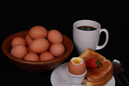 Soft boiled egg coffee and strawberry on black background photo