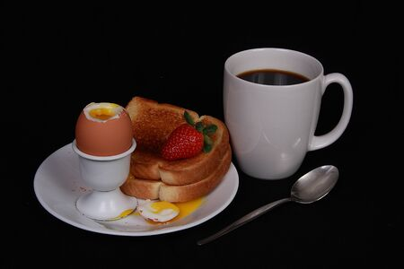 Soft boiled egg and toast coffee on black background photo