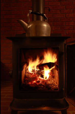 A view of a traditional wood burning stove and kettle photo
