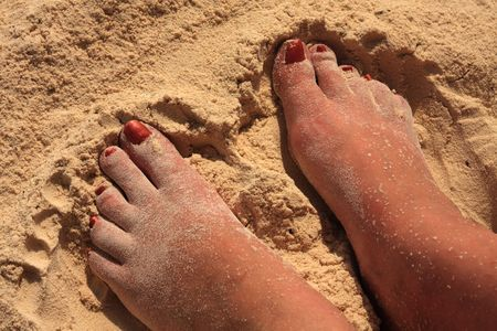 u�as pintadas: Womens pies en la arena en una playa tropical