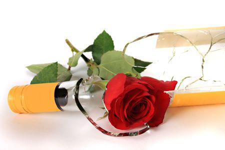 Broken wine bottle and rose on white background photo