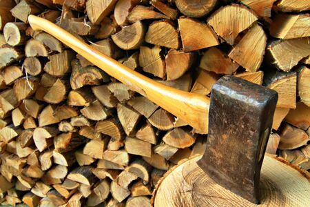 Axe set in chopping block in front of a woodpile background Stock Photo