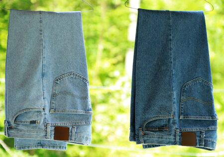 Freshly washed and ironed denim jeans hanging outside  Stock Photo
