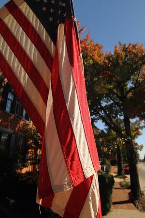 A view of a US flag in a rural fall setting
