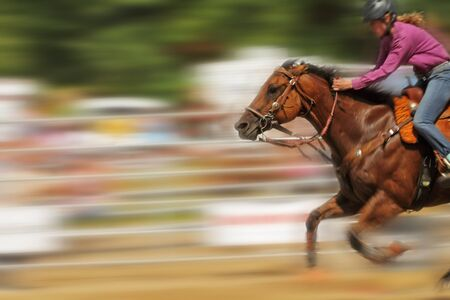 Panning shot of female racing a horse Editorial