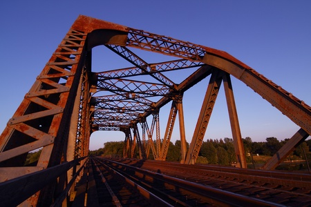 A view of a rusted steel train bridge at sunset