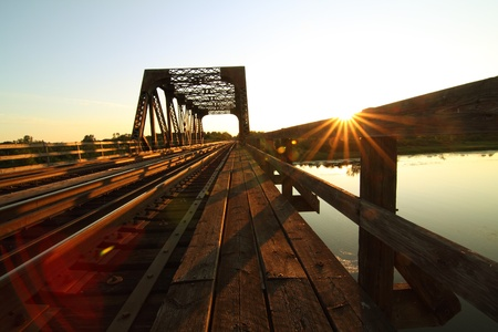 A view of a steel train bridge at sunset Stock Photo