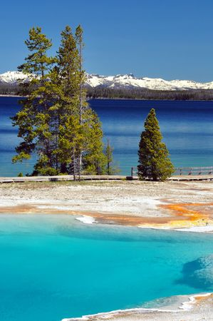 Vivid colors of a thermal pool and Yellowstone Lake on a gorgeous day. Yellowstone National Park photo