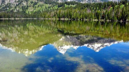 A reflection of the Grand Tetons in Taggart Lake. Grand Teton National Park, Wyoming photo