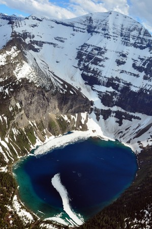 Aerial shot of half-frozen Kennedy Lake. Glacier National Park, Montana Stock Photo