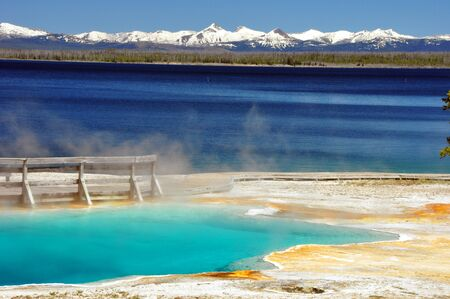 Vivid colors of a thermal pool and Yellowstone Lake on a gorgeous day. Yellowstone National Park Zdjęcie Seryjne
