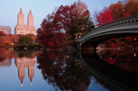 Beautiful Fall dawn in Central Park. Reflections of Bow bridge and New York Skyscrapers in the Lake.