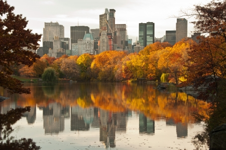 Beautiful Fall dawn in Central Park. Reflections of  New York Skyscrapers in the Lake.