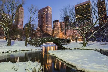 Gapstow 橋; 雪で冬にニューヨーク市マンハッタンのセントラルパーク夕暮れの湖や高層ビルの凍結