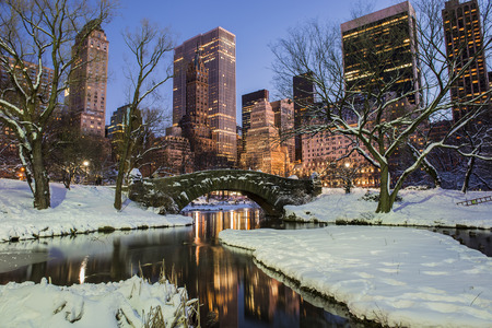 city night: New York City Manhattan Central Park in winter with snow, Gapstow bridge; freezing lake and skyscrapers at dusk
