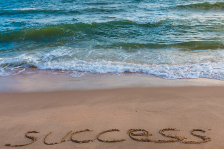 e u: alphabet letters success handwritten in sand on beach for background