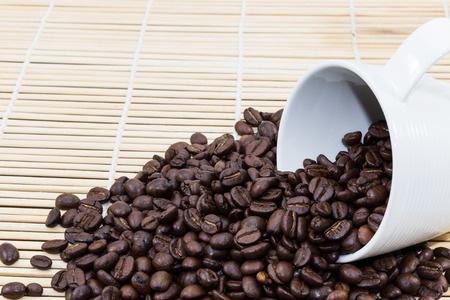 straw mat: Coffee Cup with roasted coffee beans on heap of bamboo brown straw mat for background Stock Photo