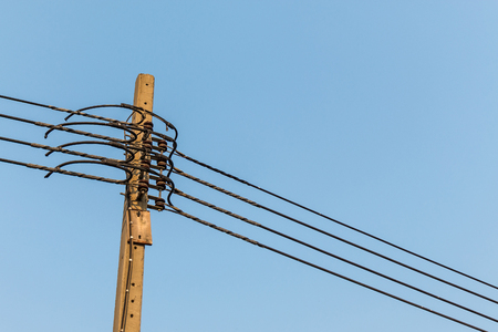 voltage gray: electricity post with clear blue sky