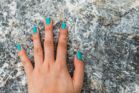 five fingers: Five fingers is blue nail on stone background