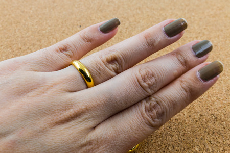 cork wood: detail of fingers with gold ring on cork wood background