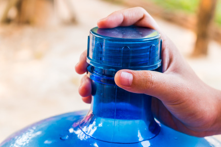 distilled water: Girl hands with a large mineral water containe