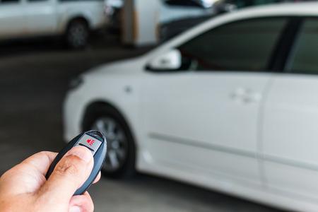 open autocar auto: Mens hand presses on the remote control car alarm systems Stock Photo