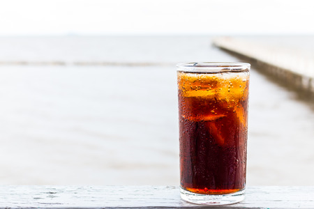 fizz: Glass of cola with ice on wooden table of the sea blackground