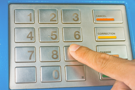 the entering: Close-up of hand entering PINpass code on ATMbank machine keypad Stock Photo