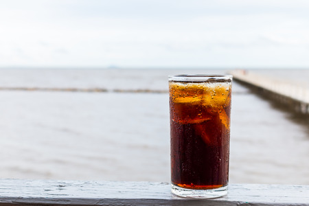 sparkling water: Glass sparkling water   with ice on wooden table of the sea blackground