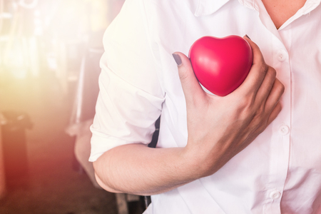 doctor holding gift: Woman holding a red heart health