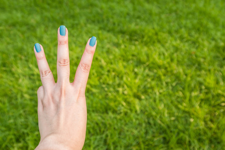 Three fingers on green background Stock Photo