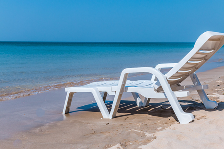 One sunbed on tropical calm beach with  sea water and white sand