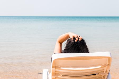 Ontspannen en genieten op zomervakantie, vrouw liggend in zonnebank op het strand Stockfoto - 74804135