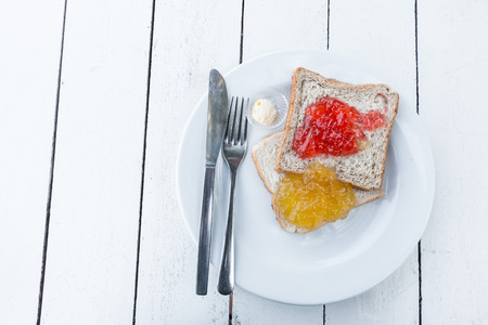 strawberry jam sandwich: Bread jam in a white plate on the table.
