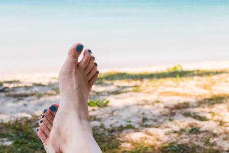 Feet of a young woman lying on the beach view a sea Foto de archivo