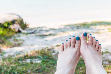 Feet of a young woman lying on the beach view a sea Banque d'images
