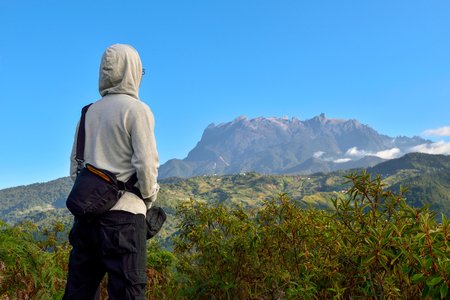 Unrecognized man on white hooded long sleeve shirt and sling bag, appreciating the beauty of nature at Bundu Tuhan, Ranau, Sabah, Malaysia in one early morning. Seen at far is the majestic Mount Kinabalu.