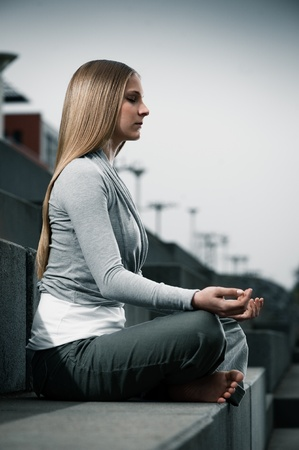 yoga pants: Young woman 20-25 sitting and meditating environment yoga meditation in a modern, cool, outdoor Stock Photo