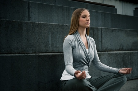Young woman 20-25 sitting and meditating environment yoga meditation in a modern, cool, outdoor Stock Photo