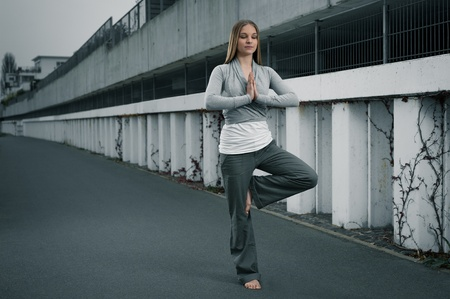 Young woman 20-25 standing and meditating environment yoga meditation in a modern, cool, outdoor photo