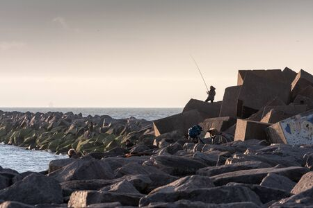 supposedly: People catch fish from the Baltic Sea breakwater. Stock Photo