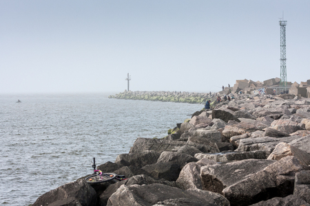 baltic people: People catch fish from the Baltic Sea breakwater. Stock Photo