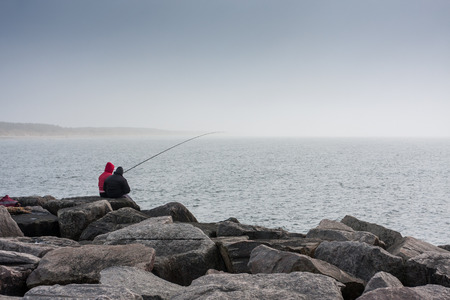 People catch fish from the Baltic Sea breakwater. 스톡 콘텐츠